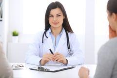 Donkerbruine vrouwelijke arts die aan patiënt op het ziekenhuiskantoor spreken De arts zegt over medische examens resultaten voor Stock Afbeelding
