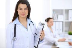 Donkerbruine vrouwelijke arts op de achtergrond van collega's die aan elkaar in het ziekenhuis spreken Royalty-vrije Stock Afbeeldingen