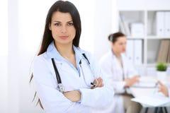 Donkerbruine vrouwelijke arts op de achtergrond van collega's die aan elkaar in het ziekenhuis spreken Royalty-vrije Stock Fotografie