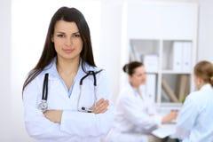 Donkerbruine vrouwelijke arts op de achtergrond van collega's die aan elkaar in het ziekenhuis spreken Royalty-vrije Stock Foto's