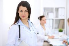 Donkerbruine vrouwelijke arts op de achtergrond van collega's die aan elkaar in het ziekenhuis spreken Royalty-vrije Stock Foto