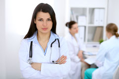 Donkerbruine vrouwelijke arts op de achtergrond van collega's die aan elkaar in het ziekenhuis spreken Royalty-vrije Stock Afbeelding