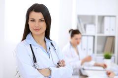 Donkerbruine vrouwelijke arts op de achtergrond van collega's die aan elkaar in het ziekenhuis spreken Stock Foto