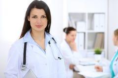 Donkerbruine vrouwelijke arts op de achtergrond van collega's die aan elkaar in het ziekenhuis spreken Stock Fotografie