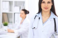 Donkerbruine vrouwelijke arts op de achtergrond van collega's die aan elkaar in het ziekenhuis spreken De arts is bereid te helpe Stock Foto