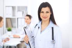 Donkerbruine vrouwelijke arts op de achtergrond van collega's die aan elkaar in het ziekenhuis spreken De arts is bereid te helpe Royalty-vrije Stock Afbeelding