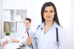 Donkerbruine vrouwelijke arts op de achtergrond van collega's die aan elkaar in het ziekenhuis spreken De arts is bereid te helpe Stock Foto's