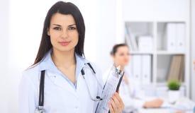 Donkerbruine vrouwelijke arts op de achtergrond van collega's die aan elkaar in het ziekenhuis spreken De arts is bereid te helpe Royalty-vrije Stock Foto