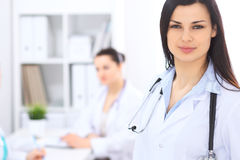 Donkerbruine vrouwelijke arts op de achtergrond van collega's die aan elkaar in het ziekenhuis spreken De arts is bereid te helpe Stock Afbeelding