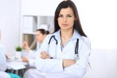 Donkerbruine vrouwelijke arts op de achtergrond van collega's die aan elkaar in het ziekenhuis spreken Geneeskunde en gezondheids Royalty-vrije Stock Foto