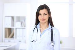 Donkerbruine vrouwelijke arts op de achtergrond van collega's die aan elkaar in het ziekenhuis spreken Geneeskunde en gezondheids Stock Afbeeldingen