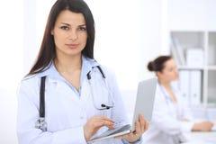 Donkerbruine vrouwelijke arts op de achtergrond van collega's die aan elkaar in het ziekenhuis spreken Geneeskunde en gezondheids Stock Fotografie