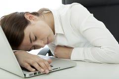 Donkerbruine vrouwendaling in slaap op haar computer stock afbeeldingen