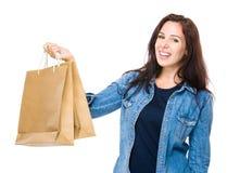 Donkerbruine vrouwengreep met het winkelen zak stock afbeeldingen