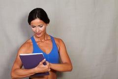 Donkerbruine vrouwenholding tablet en het werken Stock Fotografie