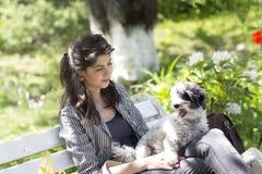 Donkerbruine vrouwenzitting op een witte bank met haar witte hond stock foto's