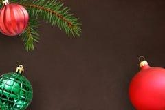 Donkere achtergrond met de tak van de Kerstmisspar, rode golvende saaie en groene geribbelde bal Stock Afbeelding