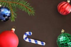 Donkere achtergrond met de tak van de Kerstmisspar, stok, blauwe, groene geribbelde en rode golvende bal Royalty-vrije Stock Foto's