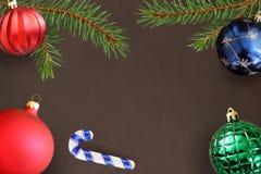 Donkere achtergrond met de tak van de Kerstmisspar, stok, rode golvende, groene geribbelde en blauwe bal Stock Fotografie