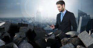 Donkere bakstenen in stapel met de telefoon van de zakenmanholding over stad Royalty-vrije Stock Foto's