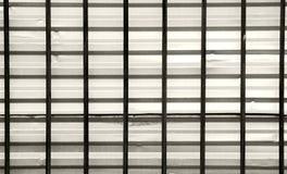 donkere bars op een achtergrond van grijs gegalvaniseerd blad, de kruising horizontaal en verticaal Stock Fotografie