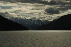Donkere bergen over een meer Stock Fotografie