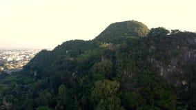 Donkere bosbouwheuvel door stad tegen heldere duidelijke hemel stock videobeelden
