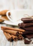 Donkere chocolade, pijpjes kaneel en een kop van koffie Stock Foto