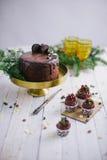 Donkere chocoladecake met koekjes en cupcakes bessen op witte houten achtergrond Stock Foto's