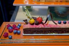 Donkere chocoladecake met vers fruitbovenste laagje en rond vertoning Stock Afbeelding