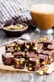 Donkere chocoladekubussen met pistaches en kop van koffie op woode Stock Foto