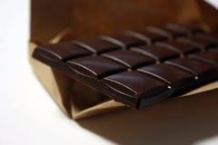Donkere chocoladereep in pak backround stock foto