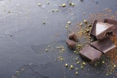 Donkere chocoladestukken en cacaopoeder over zwarte achtergrond Stock Afbeeldingen