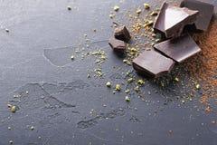 Donkere chocoladestukken en cacaopoeder over zwarte achtergrond Stock Afbeelding