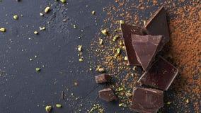 Donkere chocoladestukken en cacaopoeder over zwarte achtergrond Stock Foto's