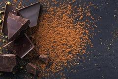 Donkere chocoladestukken en cacaopoeder over zwarte achtergrond Royalty-vrije Stock Fotografie