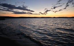 Donkere Cirruswolken bij zonsondergang over het meer Stock Foto's
