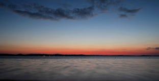 Donkere Cirruswolken bij zonsondergang over het meer Stock Afbeeldingen