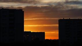 Donkere contouren van gebouwen op de achtergrond van geeloranje bewolkte hemel tijdens zonsopgang royalty-vrije stock afbeelding
