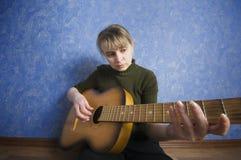 Donkere de rotsster die van de grungestijl een gitaar houdt Stock Afbeelding