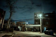 Donkere en angstaanjagende stadssteeg bij nacht stock afbeelding