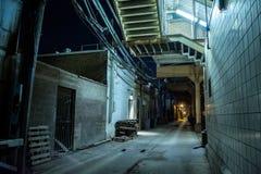 Donkere en angstaanjagende stedelijke stadssteeg bij nacht stock foto