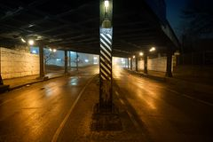 Donkere en zanderige stedelijke straatweg en uitstekende brug bij nacht stock foto's