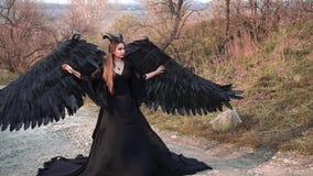 Donkere engel met grote massieve zwarte vleugels en hoornen op hoofdtribunes in midden van weg in lange vliegende uitstekende kle stock videobeelden