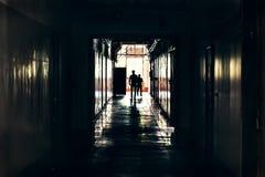 Donkere gang in de bouw, deuren en silhouetten van tweepersoons, perspectief Royalty-vrije Stock Foto
