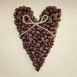Donkere geroosterde koffiebonen in de vorm van een hart met een boog Stock Fotografie