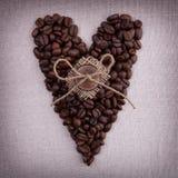 Donkere geroosterde koffiebonen in de vorm van een hart met houten B Stock Afbeelding