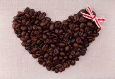 Donkere geroosterde koffiebonen in de vorm van een hart met rood BO Stock Afbeeldingen