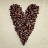Donkere geroosterde koffiebonen in de vorm van een hart op stof Royalty-vrije Stock Foto
