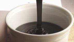 Donkere gesmolten vloeibare chocolade die langzame motie gieten stock videobeelden